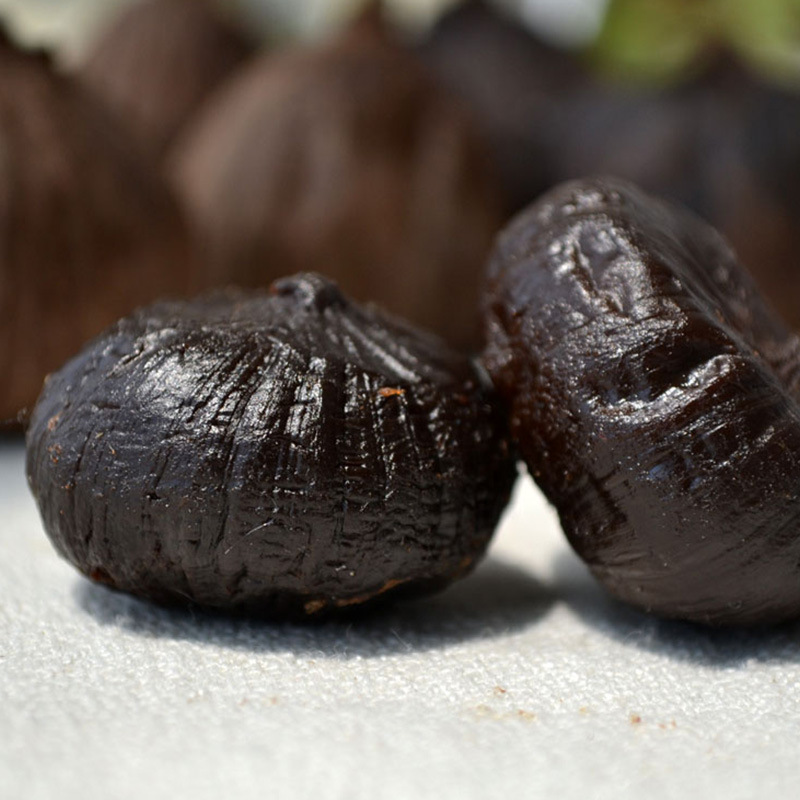 single peeled black garlic